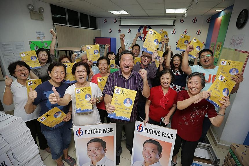 Mr Sitoh Yih Pin (centre) and Potong Pasir residents with copies of the MP's campaign manifesto which outlines his track record as well as future plans for the ward. He won the constituency for the PAP by 114 votes in the 2011 General Election.