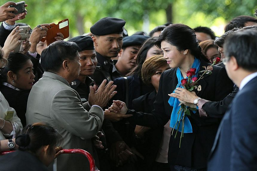 Ms Yingluck Shinawatra was handed roses by supporters as she arrived at the court yesterday for a case involving her rice subsidy scheme when she was Thailand's premier.