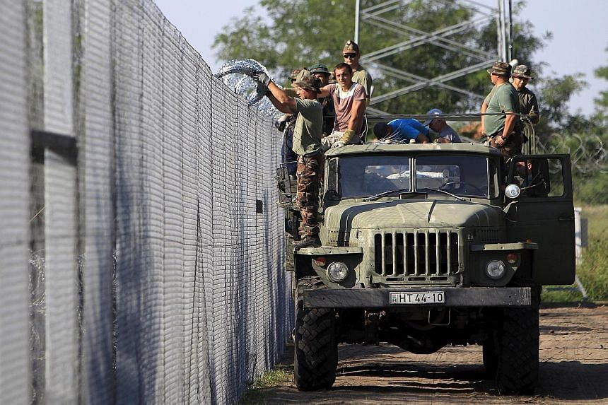 Hungarian soldiers adjusting razor wire on a fence near the town of Asotthalom on Sunday. Analysts say tall fences will not keep out the migrants, who travel in groups, often guided by Google Maps and Facebook on the smartphones that are vital to thi