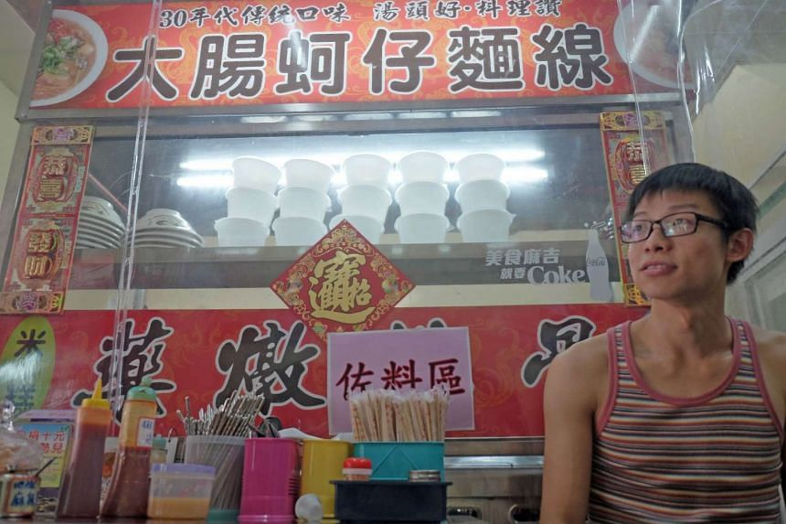 Carlos Cheung, 28, a Hong Kong emigrate to Taiwan, poses in front of his food stall in central Taichung on July 24, 2015. Squeezed by soaring rents, cramped living conditions, and unease over their city's political future, a growing number of Hong Ko