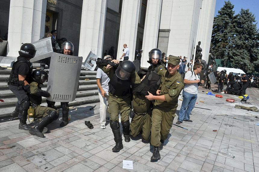Ukrainian national guard officers carry an injured colleague to an ambulance outside the parliament building in Kiev, Ukraine on Aug 31, 2015.