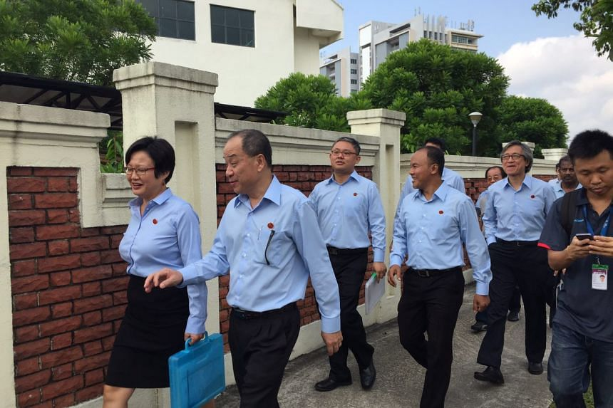 Workers' Party chairman Ms Sylvia Lim (left) and chief Low Thia Khiang leading candidates into Raffles Institution.