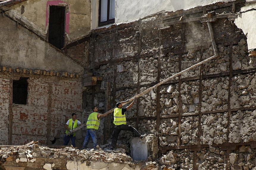Construction workers trying to bring down a beam in downtown Madrid, Spain, on July 23, 2015.