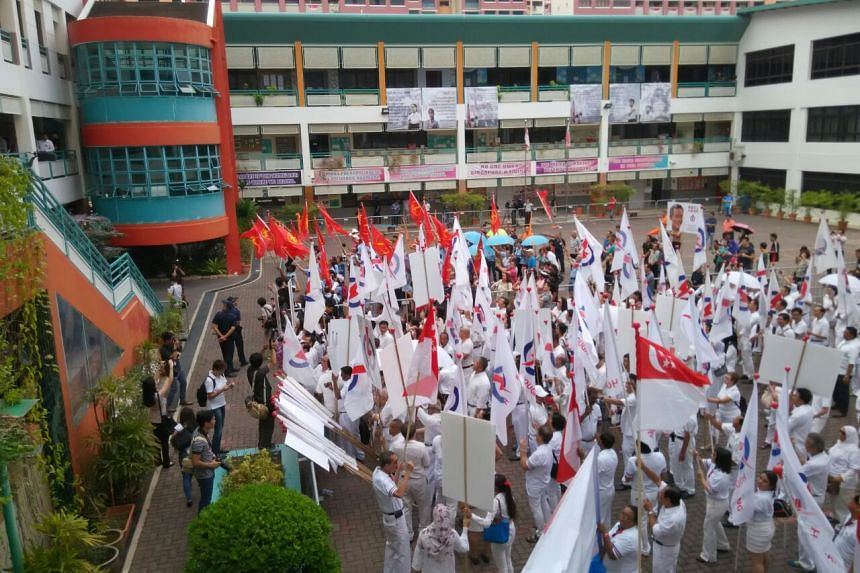 Party banners being unfurled at Poi Ching School, the nomination centre for Aljunied, Ang Mo Kio and Bishan-Toa Payoh GRCs.