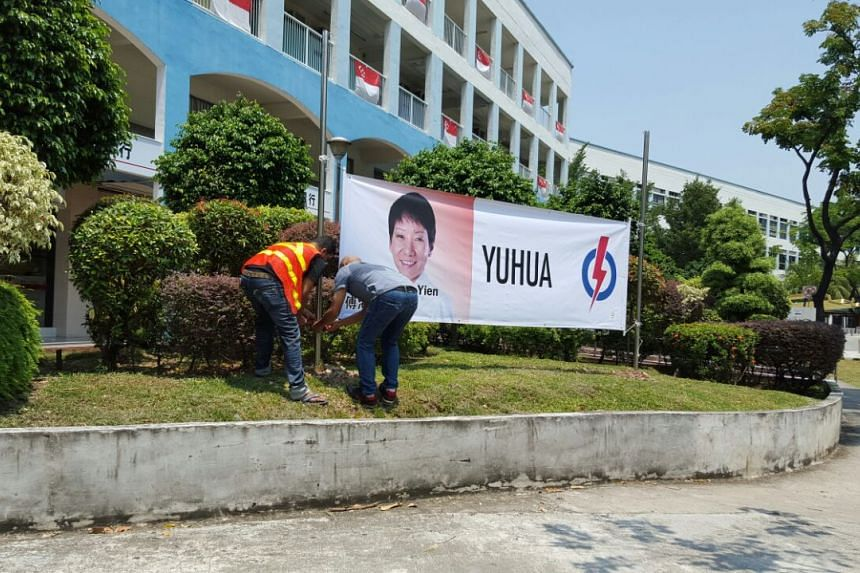 Workers putting up a banner of Ms Grace Fu, the PAP's candidate in Yuhua, at Jurong East St 13.