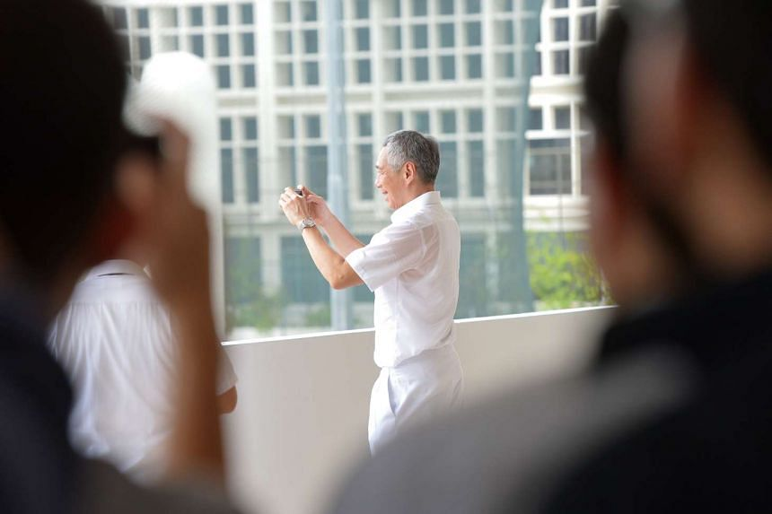 Prime Minister Lee Hsien Loong taking a photo of supporters at Raffles Institution.