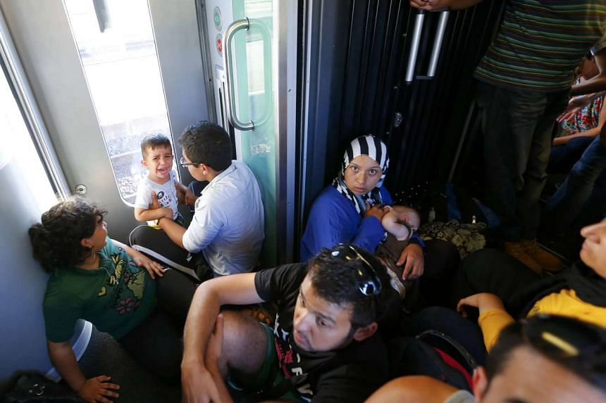 Travellers sit and stand in a train with migrants on board, en route from Budapest to Vienna, Austria on Monday.