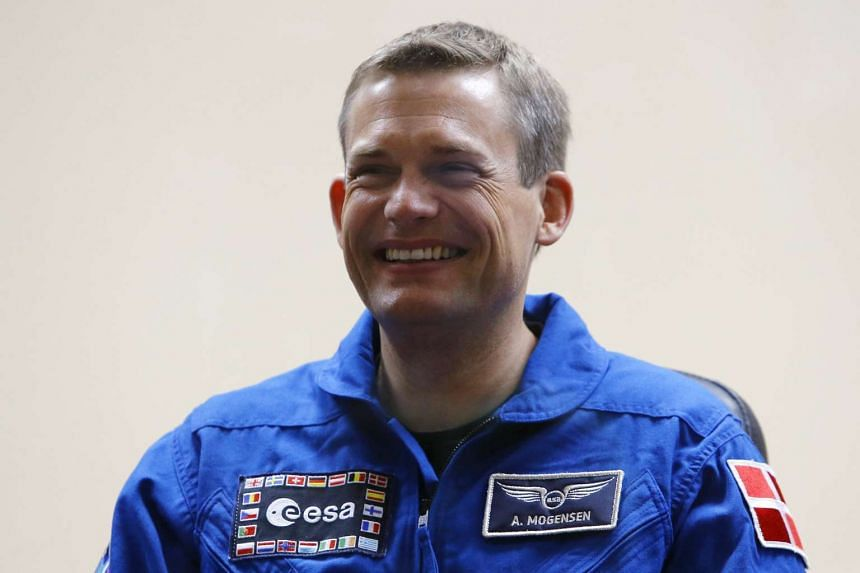 Danish astronaut Andreas Mogensen smiles behind a glass wall during a news conference at Baikonur cosmodrome, Kazakhstan, on Wednesday.