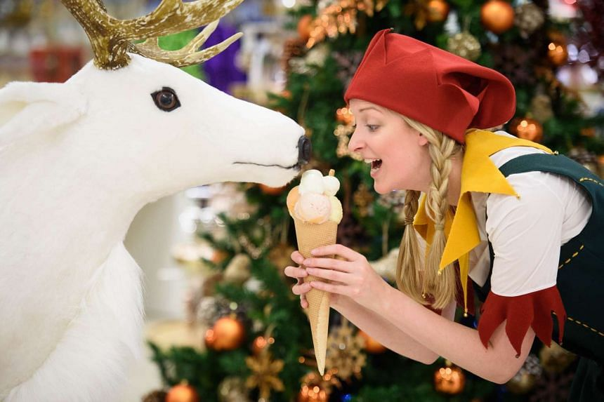 A Christmas elf poses with an ice cream and a toy reindeer during a promotional event to launch the Selfridges Christmas Shop in their flagship store in central London on Aug 3. With 142 shopping days until Christmas, Selfridges is the first store to