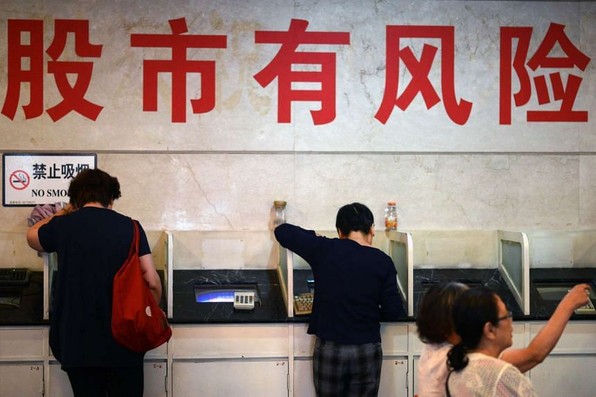 This July 6, 2015 file photo shows Stock investors as they check computers under Chinese writing which translates as 'stock market has risk' at a brokerage house in Shanghai in a July 6 file photo. The United States is reportedly drawing up economic