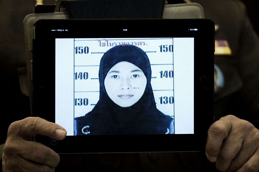 Thailand's national police spokesman Prawut Thavornsiri holds a tablet displaying a picture of Wanna Suansan, 26, wanted for questioning after bomb making materials were found in a Bangkok apartment she allegedly rented, at the police headquarters in