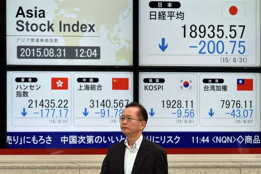 A Japanese businessman walks past a share prices board showing the numbers at the Tokyo Stock Exchange and other regional markets, in Tokyo on Aug 31, 2015.