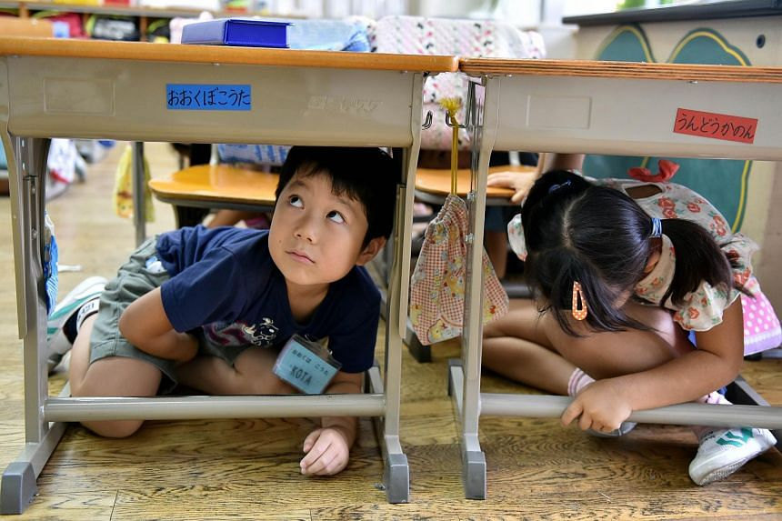 Elementary school children take cover under their desks during an earthquake drill at a school in Tokyo on Sept 1, 2015.