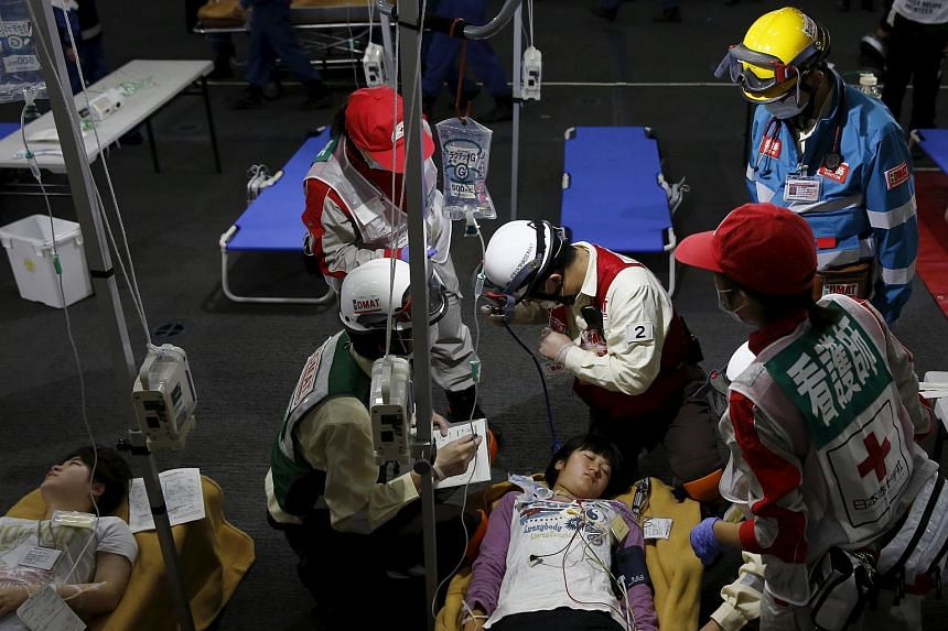 """Medics treat a """"victim"""" during an emergency drill on Japan's national """"Disaster Prevention Day"""" onboard the Izumo military helicopter carrier in Tokyo on Sept 1, 2015."""