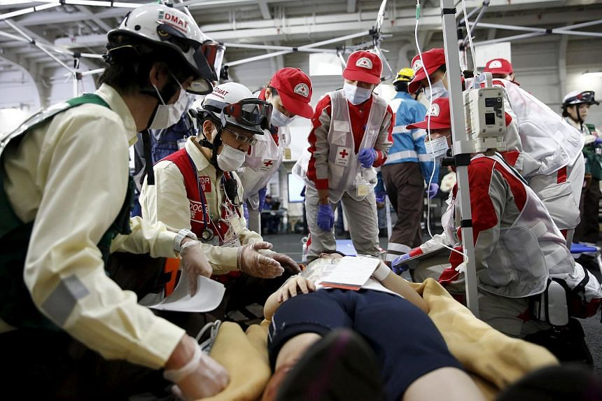 """A doctor and medics discuss emergency procedures on a """"victim"""" during an emergency drill on Japan's national """"Disaster Prevention Day"""" on Sept 1, 2015."""