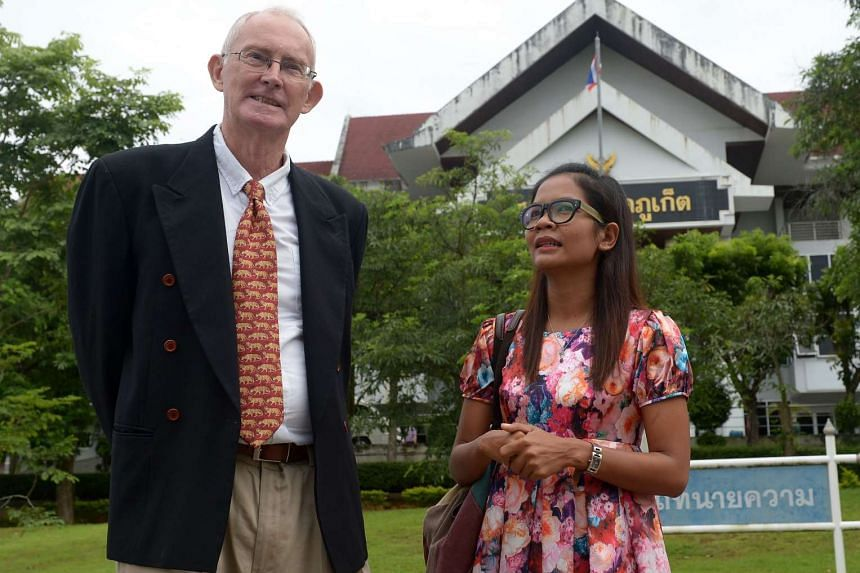 Australian journalist Alan Morison (left) talks with Thai colleague Chutima Sidasathian during their arrival at the provincial court in Phuket island on Sept 1, 2015.