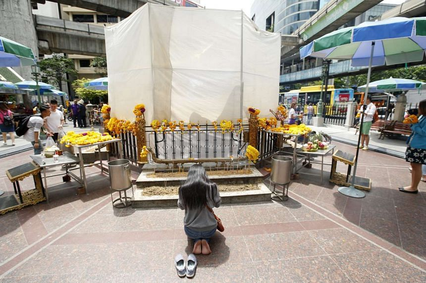 A woman prays before the Erawan shrine, covered for renovation and repair after the Aug 17 bomb blast, in Bangkok on Sept 1, 2015.