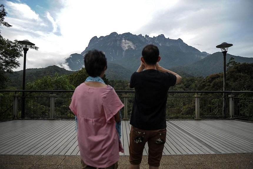A tourist taking pictures of Malaysia's Mount Kinabalu.