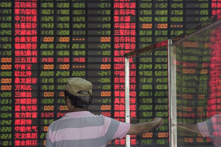 An investor looks on in front of a digital board showing stock market movements at a brokerage house in Shanghai.