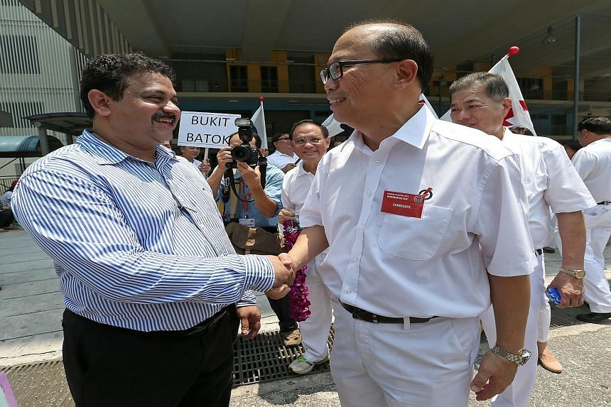Mr Samir Salim Neji (at far left) greeting the PAP's Mr David Ong. SDP's Mr Sadasivam Veriyah (above) joins them in the three-way fight.