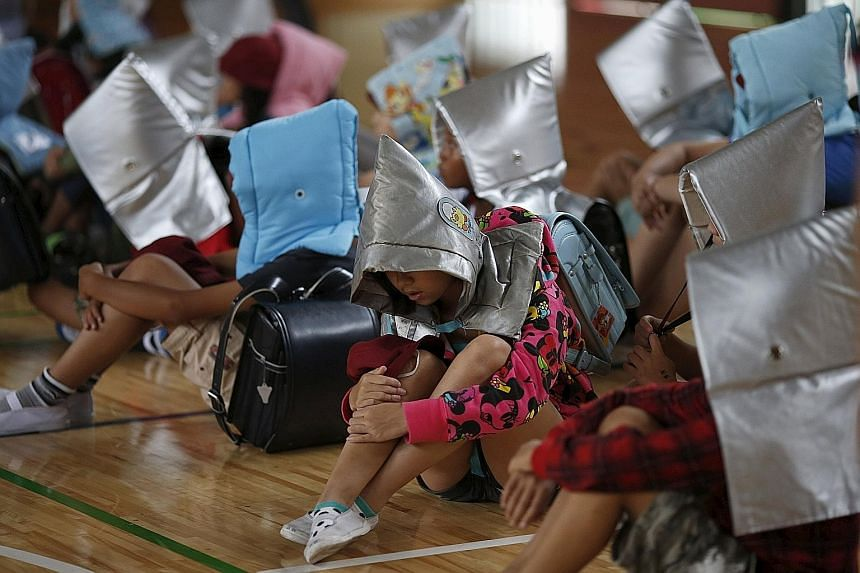 School children, wearing padded hoods to protect them from falling debris, sit in a gymnasium during an earthquake simulation exercise at an elementary school in Tokyo yesterday. The annual exercise is held nationwide, on the anniversary of the 1923