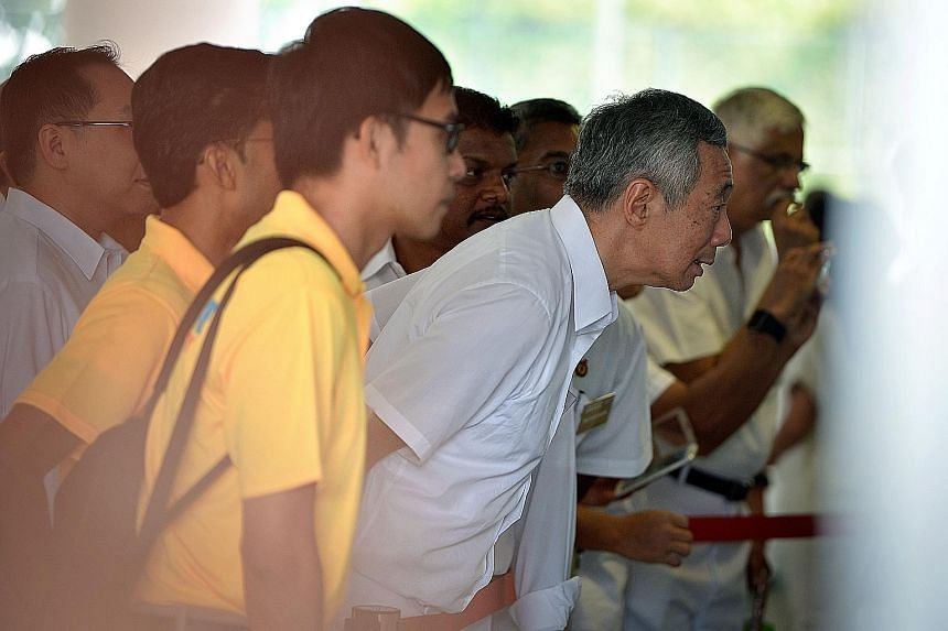 PM Lee Hsien Loong (left) and activist Roy Ngerng (with bag) checking the nomination papers outside the RI school hall yesterday. PM Lee will lead the PAP team against Mr Ngerng's Reform Party in Ang Mo Kio GRC.