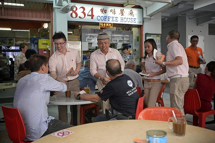 NSP candidates for Sembawang GRC (from left) Spencer Ng, Yadzeth Haris, Kevryn Lim and Eugene Yeo meeting residents at a coffee shop at Block 834, Woodlands Street 83, yesterday.