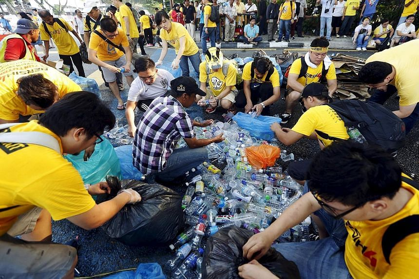 Protesters sorting out trash for recycling during last weekend's Bersih rally in Kuala Lumpur. A government minister said yesterday the rally organisers will be billed by the Urban Wellbeing, Housing and Local Government Ministry for the cost of clea