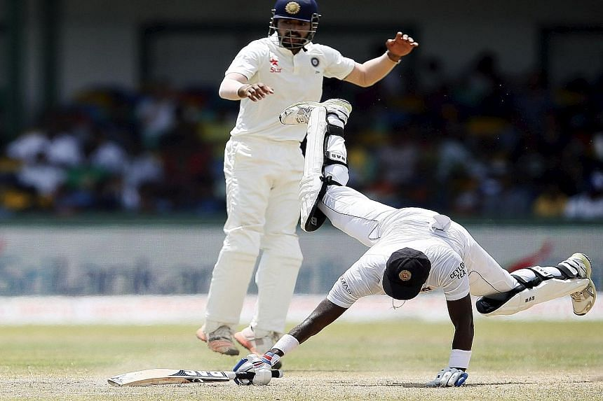 Sri Lanka's captain Angelo Mathews (right) dives back to avoid a run out as India's wicketkeeper Naman Ojha tries to catch him out during the final day of their third and final Test in Colombo. His eventual score of 110 represents his seventh Test ce