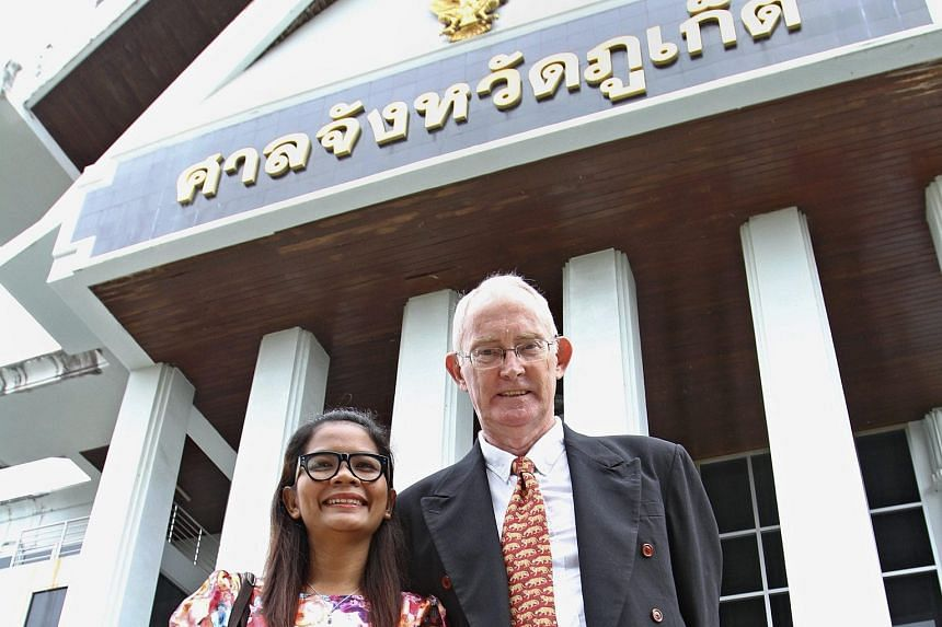 Mr Alan Morison, editor of the Phuketwan website, and reporter Chutima Sidasathian outside the provincial court in Phuket yesterday. They were facing up to seven years in jail.