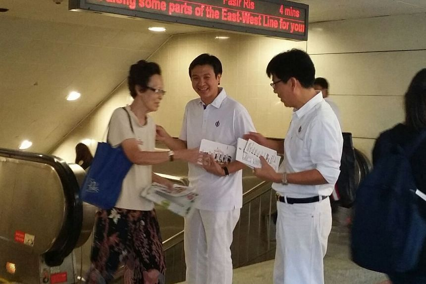 PAP's Chia Shi-Lu (centre) giving out flyers outside Tiong Bahru MRT.