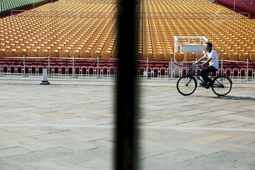 A man cycling past stands raised at Beijing's Tiananmen Square on Sept 2, 2015, as the capital prepares for the parade.