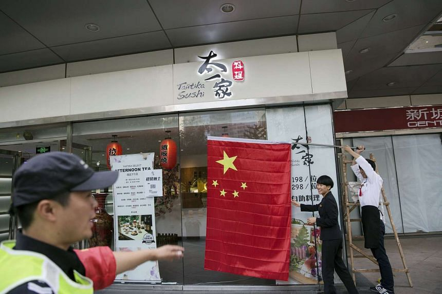 A Chinese flag is placed outside a sushi bar in central Beijing Sept 2, 2015, as people in the capital prepare to mark the end of World War II.