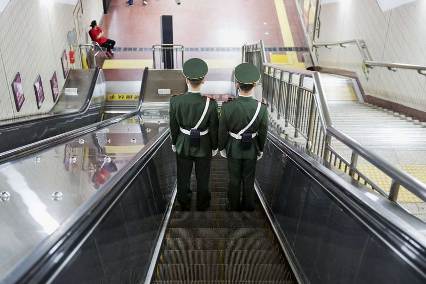 Paramilitary policemen on escalators under Beijing's Tiananmen Square on Sept 2, 2015.