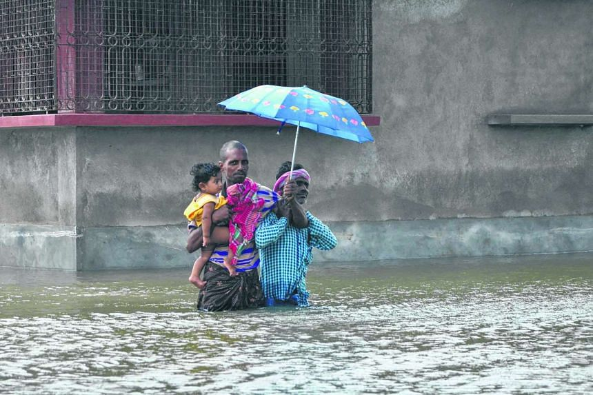 Indian villagers wading through floodwaters in Bherampur Block, Murshidabad District as the remnants of Cyclone Komen carrying heavy monsoon rains cross the eastern Indian state of West Bengal.