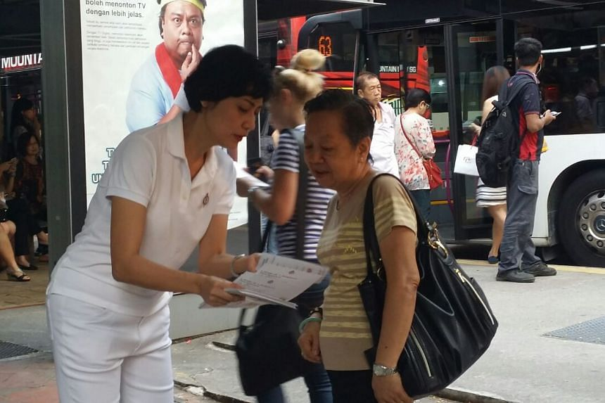 PAP's Joan Pereira speaking to a resident near a bus stop opposite Tiong Bahru Plaza.