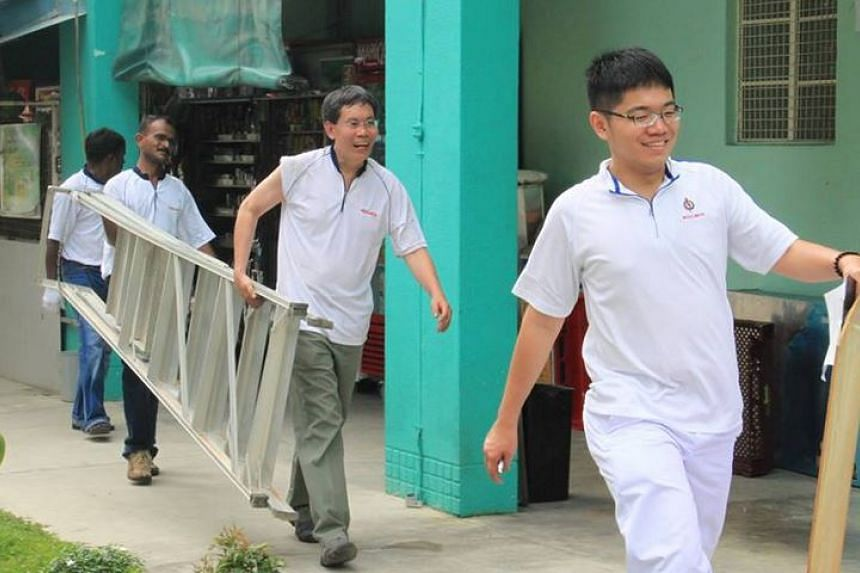 Mr Lui Tuck Yew (centre) carrying a ladder on his way to put up election posters.