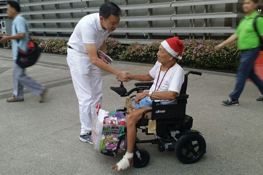 Mr Melvin Yong, of the PAP team for Tanjong Pagar GRC, speaking to an elderly resident near Tiong Bahru MRT.
