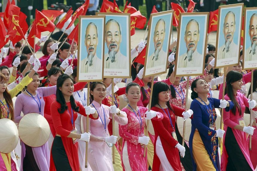 Vietnamese women, wearing traditional ao dai, carry portraits of late Vietnamese revolutionary leader Ho Chi Minh during a parade marking the country's 70th National Day at Ba Dinh square in Hanoi on Sept 2, 2015.