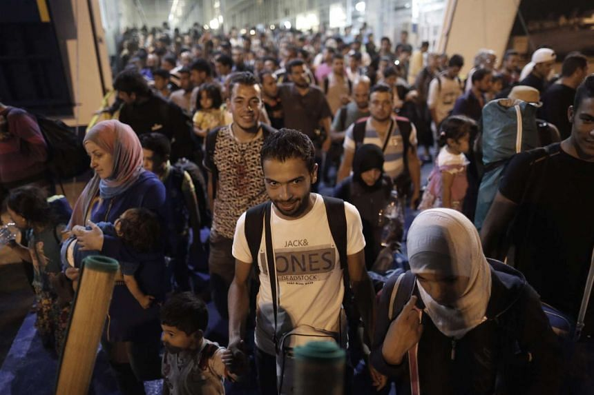 Syrian refugees disembark from a ferry at the port of Piraeus, near Athens, Greece, on Sept 1,2015.