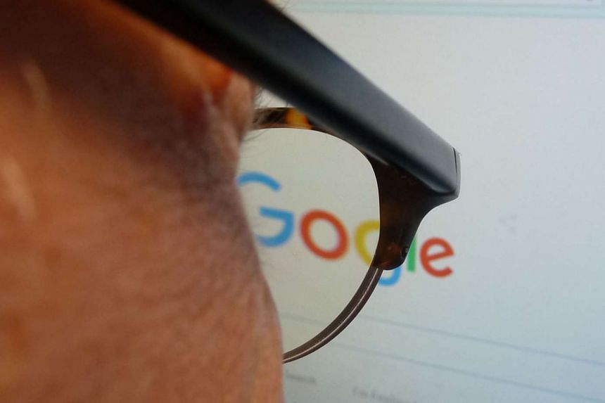 A journalist looks at the new Google logo at his work station in Washington, DC on Tuesday.