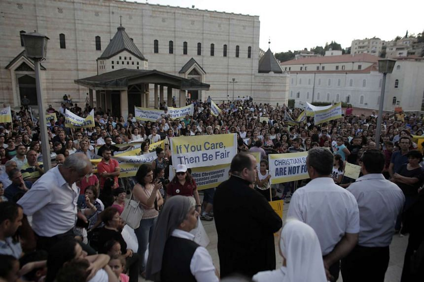Hundreds of Israeli Christians hold banners in a rally against what they said was state discrimination in funding their schools at the foot of the Basilica of the Annunciation in Nazareth on Tuesday.