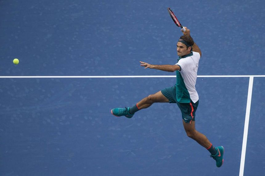 Roger Federer of Switzerland rises in the air as he prepares to hit a smash to Leonardo Mayer of Argentina during their first round match at the US Open Championships tennis tournament in New York on Tuesday.