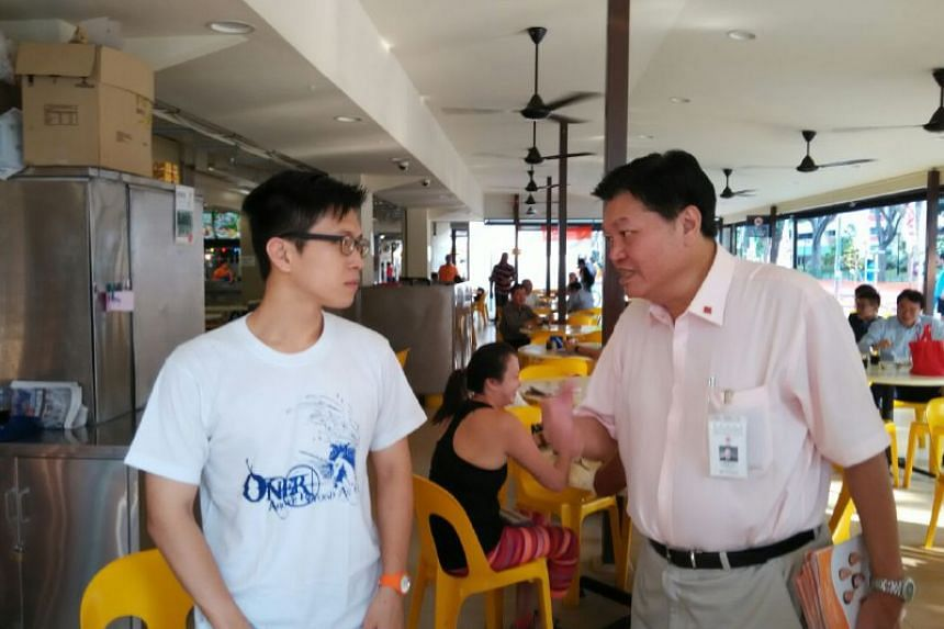 NSP's Sebastian Teo (right) speaking to a resident in Tampines Street 11.