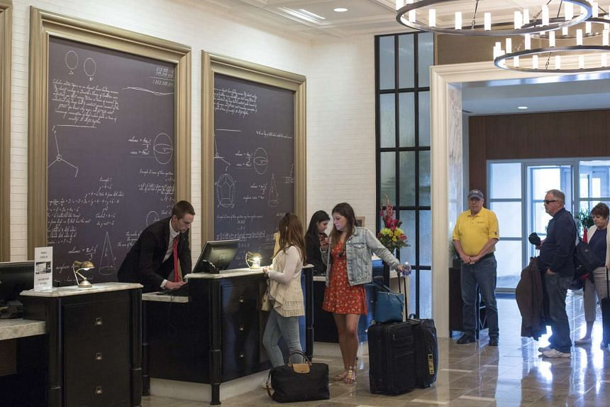 Guests checking in at a hotel. Many hotel chains are using reward points to lure travellers to book with them directly.