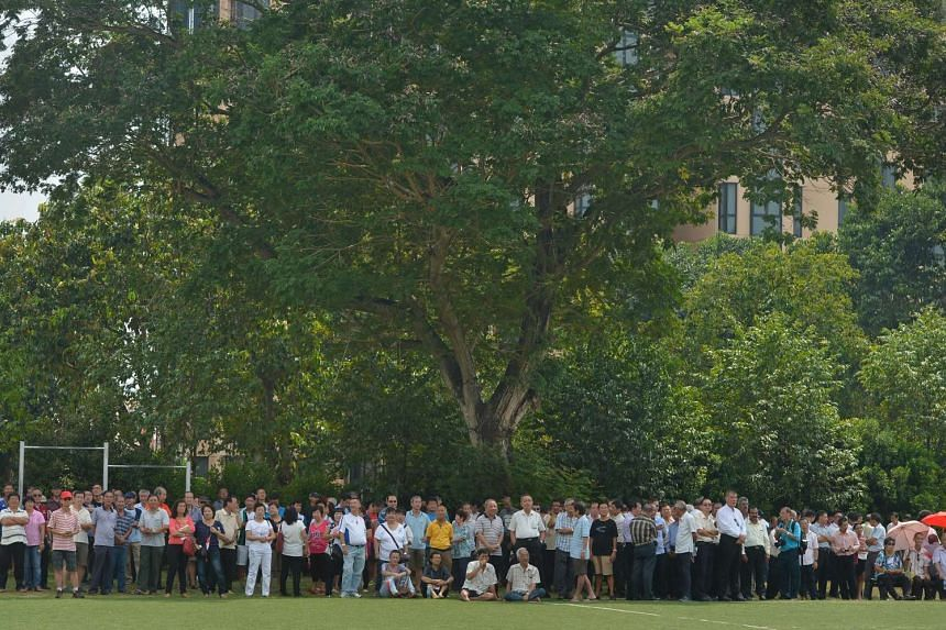 Party supporters took shelter under the shade of a large tree at Raffles Institution.