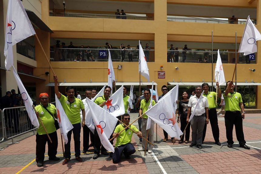 Singapore Democratic Alliance supporters (above) outside the Fengshan Primary School compound, where the SDA team filed nomination forms to contest Pasir Ris- Punggol GRC, facing a PAP team led by Deputy Prime Minister Teo Chee Hean.