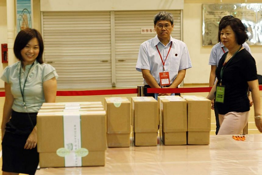 Workers' Party's Png Eng Huat standing by sealed boxes containing overseas votes during the Hougang by-election in 2012.