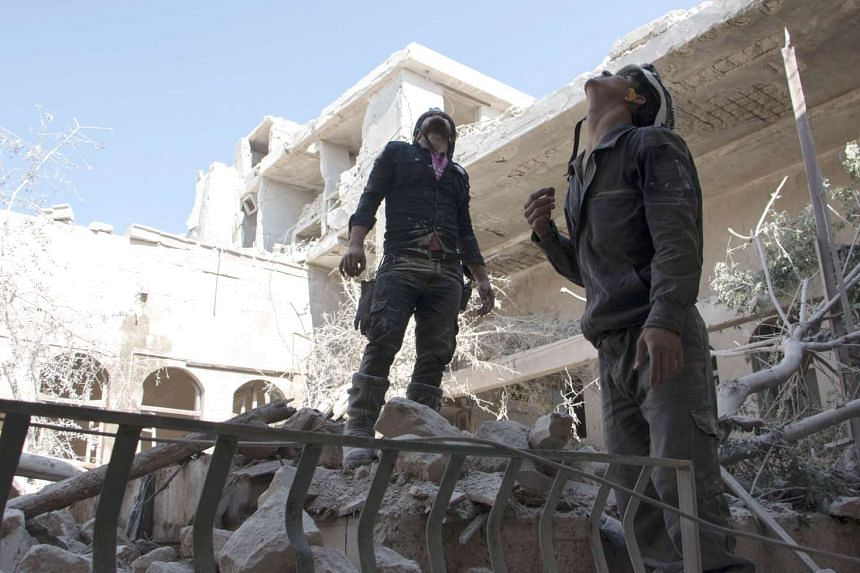 Rescue workers on June 14, 2015, in Aleppo, following a barrel bomb attack by Syrian government forces, which have often struck schools, hospitals and markets in Syria.
