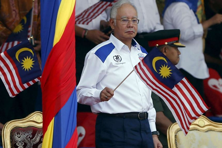 Malaysian Prime Minister Najib Razak waving a national flag during Independence Day celebrations in Kuala Lumpur on Aug 31.